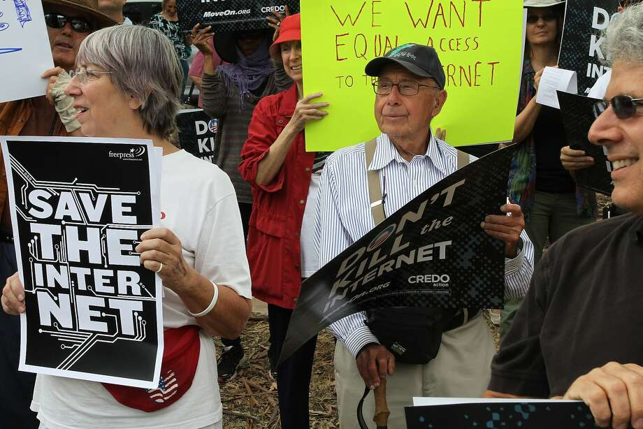 Larry Aronson, center, looks on as protesters chant about net neutrality on Page Mill Rd. on Wednesday, July 23, 2014 in Los Altos, Calif. Protesters interested in net neutrality and conflicts abroad gathered at the corner of Page Mill Rd. and Arastadero to express their concerns. Photo: James Tensuan, The Chronicle
