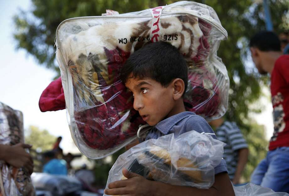A Palestinian boy carries blankets donated to a U.N. school in Gaza, where dozens of families have sought refuge from fighting. Photo: Lefteris Pitarakis, Associated Press