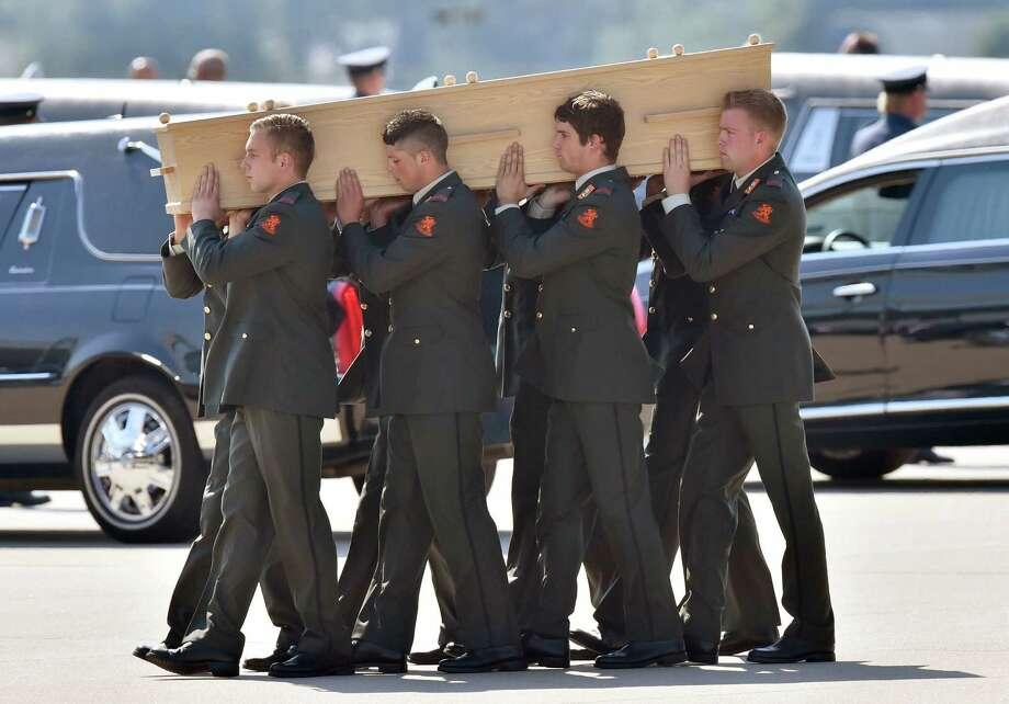Dutch military men carry coffins containing the remains of victims of downed Malaysia Airlines flight MH17, during a ceremony at Eindhoven Airbase on July 23, 2014, after a Hercules transport plane carrying the coffins landed from Ukraine.  Photo: JOHN THYS, AFP/Getty Images / AFP