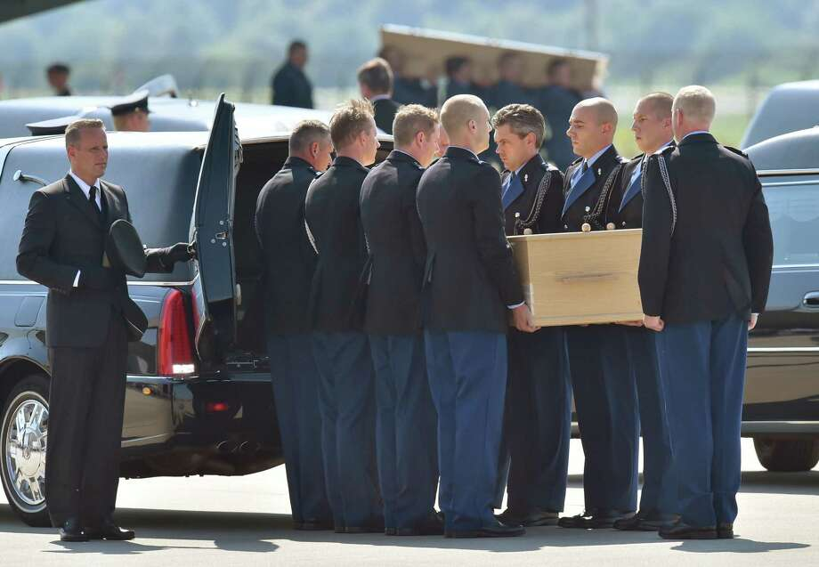 Dutch military men carry a coffin containing the body of a victim of downed Malaysia Airlines flight MH17, during a ceremony at Eindhoven Airbase on July 23, 2014, after a Hercules transport plane carrying the coffins landed from Ukraine.  Photo: JOHN THYS, AFP/Getty Images / AFP