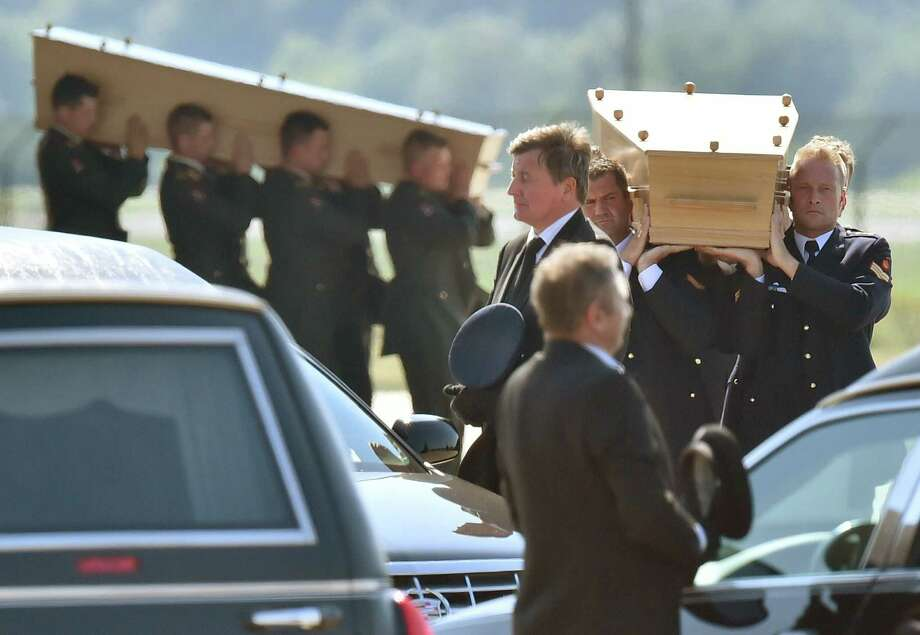 Dutch military men carry coffins containing the bodies of victims of downed Malaysia Airlines flight MH17, during a ceremony at Eindhoven Airbase on July 23, 2014, after a Hercules transport plane carrying the coffins landed from Ukraine.  Photo: JOHN THYS, AFP/Getty Images / AFP