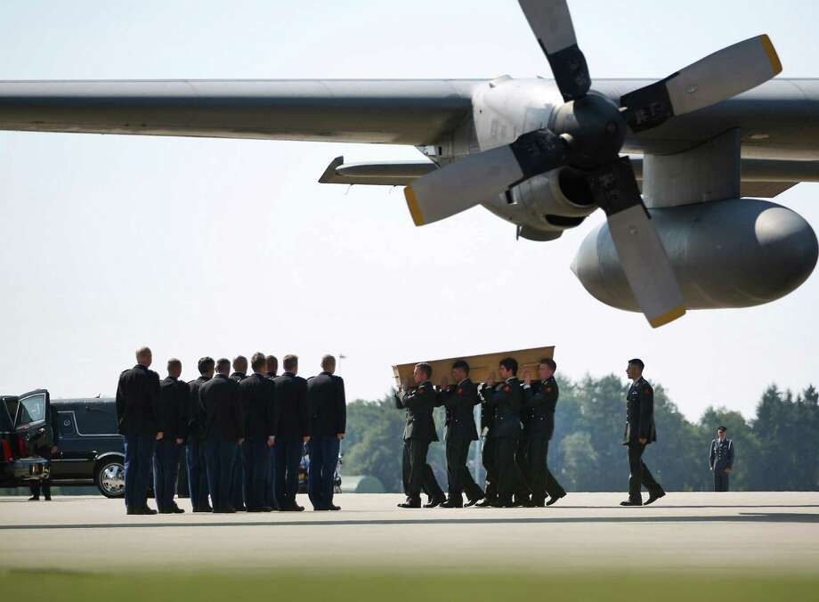 Dutch military personnel carry a coffin containing an unidentified body from the crash of Malaysia Airlines flight MH17 under the wing of a Royal Dutch Air Force C130 on July 23, 2014 in Eindhoven, Netherlands. Today the people of the Netherlands are holding a national day of mourning.  Photo: Peter Macdiarmid, Getty Images / 2014 Getty Images