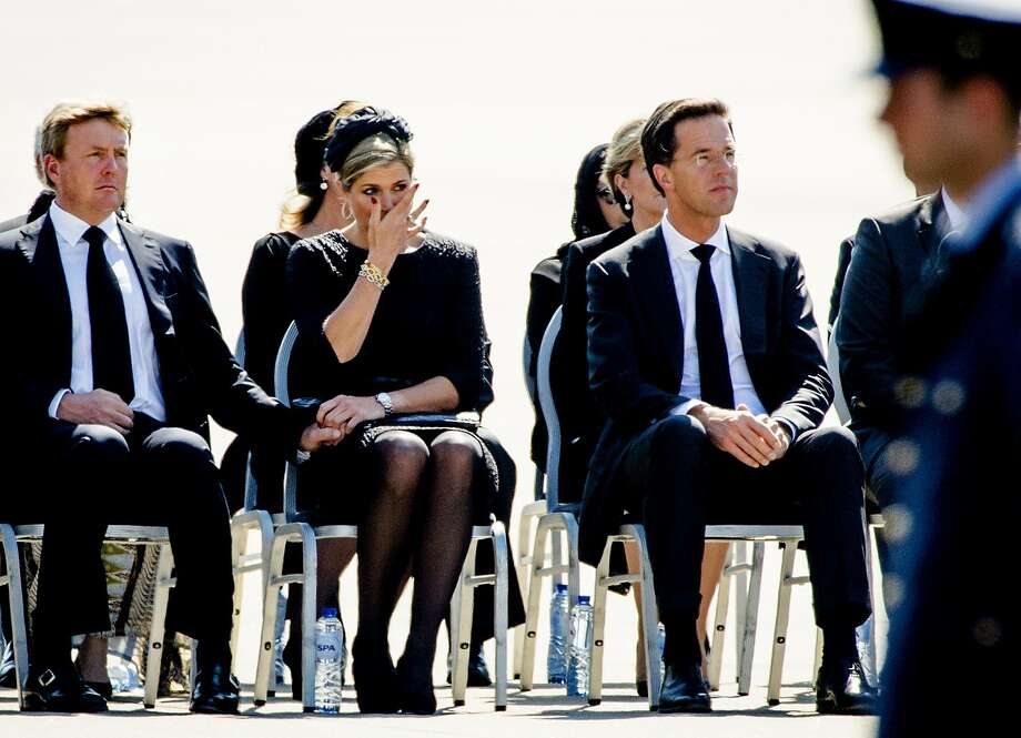 (From Left) King Willem-Alexander and Queen Maxima of The Netherlands, and Dutch Prime minister Mark Rutte attend a ceremony upon the arrivals of a plane from Ukraine, carrying the remains of victims of downed Malaysia Airlines flight MH17, at Eindhoven Airbase on July 23, 2014. Photo: ROBIN VAN LONKHUIJSEN, AFP/Getty Images / AFP