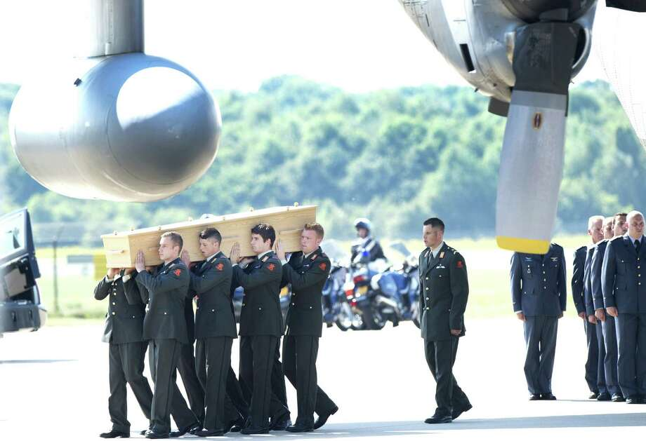 Military men carry a coffin containing the remains of a victim of downed Malaysia Airlines flight MH17, during a ceremony at Eindhoven Airbase on July 23, 2014, after a Hercules transport plane carrying the coffins landed from Ukraine. Photo: ROBIN VAN LONKHUIJSEN, AFP/Getty Images / AFP