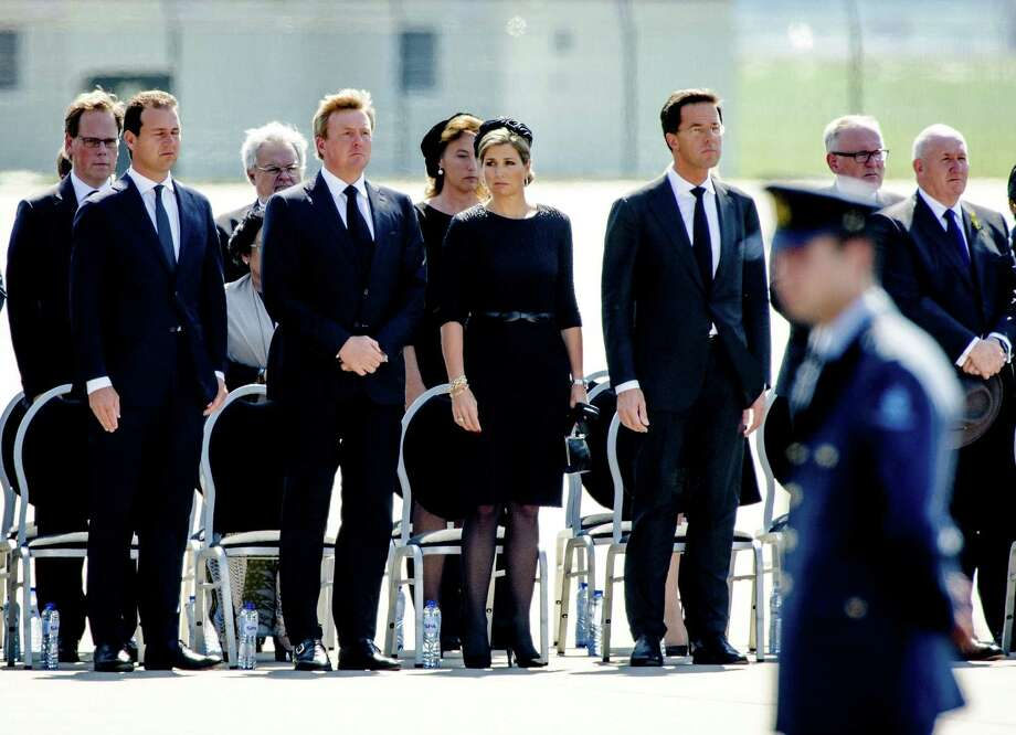 (From Left) Minister Lodewijk Asscher, King Willem-Alexander and Queen Maxima of The Netherlands, and Dutch Prime minister Mark Rutte hold a minute's silence as they attend a ceremony upon the arrivals of a plane from Ukraine, carrying the remains of victims of downed Malaysia Airlines flight MH17, at Eindhoven Airbase on July 23, 2014. Photo: ROBIN VAN LONKHUIJSEN, AFP/Getty Images / AFP