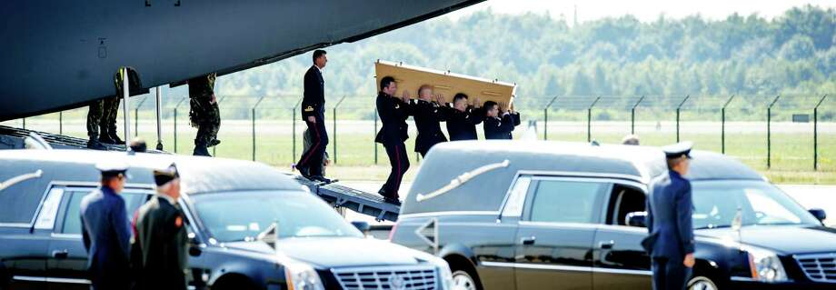 Dutch military men carry a coffin containing the remains of a victim of downed Malaysia Airlines flight MH17, during a ceremony at Eindhoven Airbase on July 23, 2014, after a Hercules transport plane carrying the coffins landed from Ukraine. Photo: ROBIN VAN LONKHUIJSEN, AFP/Getty Images / AFP