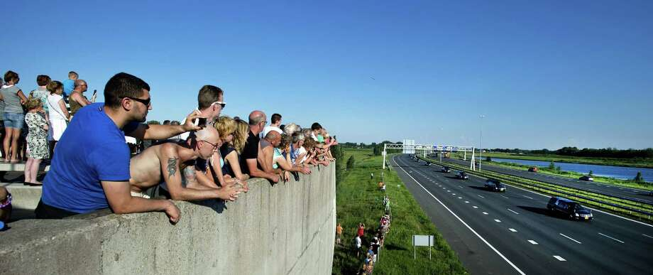 Mourners watch from a bridge a convoy of hearses carrying coffins containing the remains of victims of the downed Malaysia Airlines flight MH17, driving near Culemborg, from the Eindhoven Airbase to Hilversum on July 23, 2014, after a ceremony following the arrival of a Dutch Air Force C-130 Hercules plane and an Australian Royal Australian Air Force C17 transport plane with the first bodies of the 298 victims of the Malaysia Airlines MH17 plane crash in eastern Ukraine.  Photo: OLAF KRAAK, AFP/Getty Images / AFP