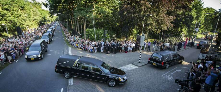 The convoy of hearses carrying coffins containing the remains of victims of the downed Malaysia Airlines flight MH17 arrives at the Korporaal van Oudheusden Kazerne in front a crowd of people lined up along the road, on July 23, 2014 in Hilversum, the Netherlands.  Photo: VINCENT JANNINK, AFP/Getty Images / AFP