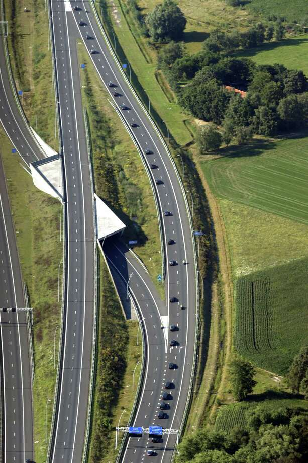 This aerial photo shows a convoy of hearses carrying coffins containing the remains of victims of the downed Malaysia Airlines flight MH17, driving from the Eindhoven Airbase to Hilversum on July 23, 2014, after a ceremony following the arrival of a Dutch Air Force C-130 Hercules plane and an Australian Royal Australian Air Force C17 transport plane with the first bodies of the 298 victims of the Malaysia Airlines MH17 plane crash in eastern Ukraine. Photo: JERRY LAMPEN, AFP/Getty Images / AFP