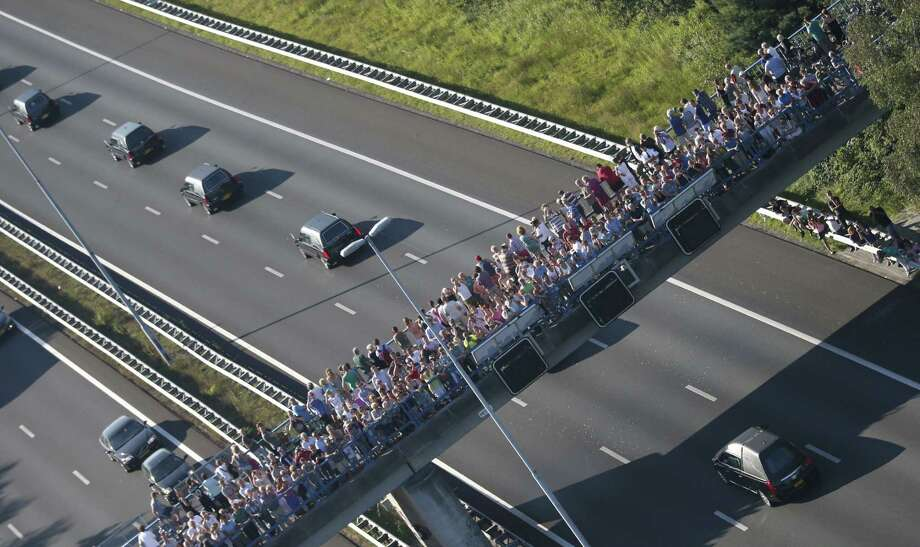 This aerial photo shows people watching from a bridge a convoy of hearses carrying coffins containing the remains of victims of the downed Malaysia Airlines flight MH17, driving from the Eindhoven Airbase to Hilversum on July 23, 2014, after a ceremony following the arrival of a Dutch Air Force C-130 Hercules plane and an Australian Royal Australian Air Force C17 transport plane with the first bodies of the 298 victims of the Malaysia Airlines MH17 plane crash in eastern Ukraine.  Photo: JERRY LAMPEN, AFP/Getty Images / AFP