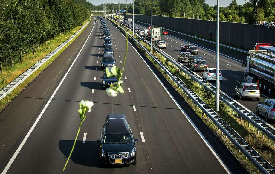 A convoy of hearses carrying coffins containing the remains of victims of the downed Malaysia Airlines flight MH17, drives from the Eindhoven Airbase to Hilversum on July 23, 2014, after a ceremony following the arrival of a Dutch Air Force C-130 Hercules plane and an Australian Royal Australian Air Force C17 transport plane with the first bodies of the 298 victims of the Malaysia Airlines MH17 plane crash in eastern Ukraine.  Photo: REMKO DE WAAL, AFP/Getty Images / AFP