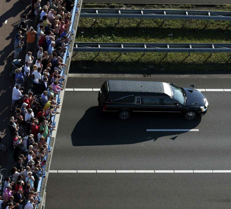 Mourners watch from a bridge a convoy of hearses carrying coffins containing the remains of victims of the downed Malaysia Airlines flight MH17, driving from the Eindhoven Airbase to Hilversum on July 23, 2014, after a ceremony following the arrival of a Dutch Air Force C-130 Hercules plane and an Australian Royal Australian Air Force C17 transport plane with the first bodies of the 298 victims of the Malaysia Airlines MH17 plane crash in eastern Ukraine.  Photo: JERRY LAMPEN, AFP/Getty Images / AFP