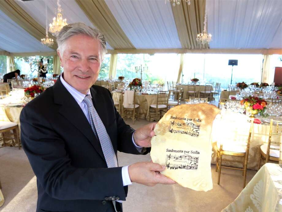 Restaurateur Piero Selvaggio displays a creation by Chef Chiarello: a flatbread he painted musical notes upon with squid ink. Photo: Catherine Bigelow