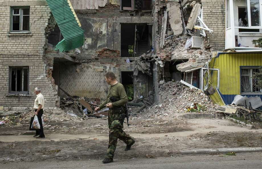 A pro-Russia rebel and a local resident walk past an apartment building recently damaged by rocket fire in Snizhne, Ukraine. Two Ukrainian military fighter jets were shot down by pro-Russian separatists in the eastern area of the country Wednesday. Photo: Rob Stothard / Getty Images / 2014 Getty Images