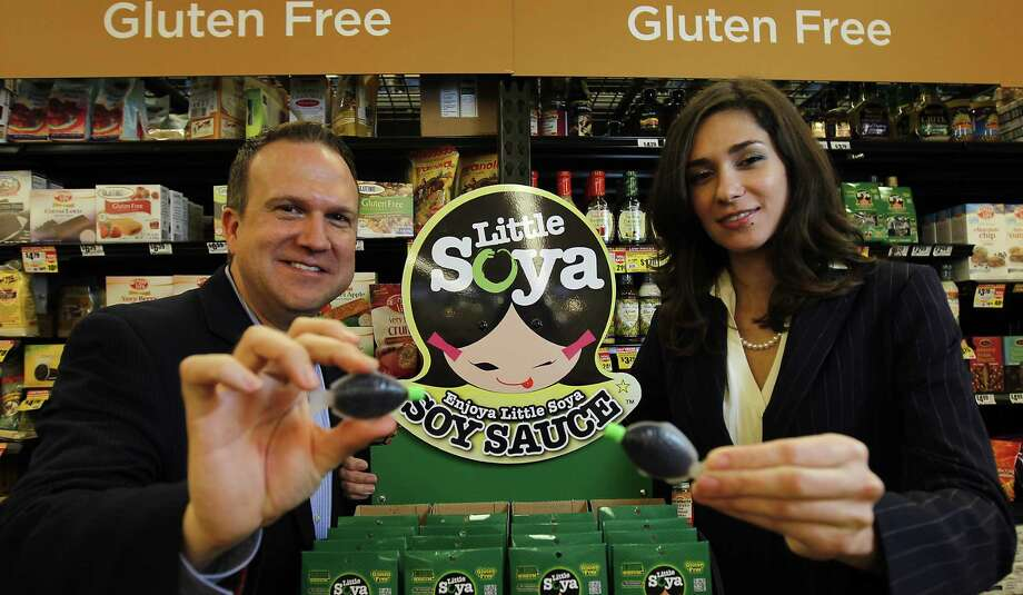 Gary Murphy, president and CEO of Little Products Company, and Crystal Lee, global accounts manager, hold the signature fish-shaped, single-serving containers of Little Soya gluten-free soy sauce at the Bunker Hill H-E-B in Houston. Photo: Karen Warren / Houston Chronicle / © 2012  Houston Chronicle