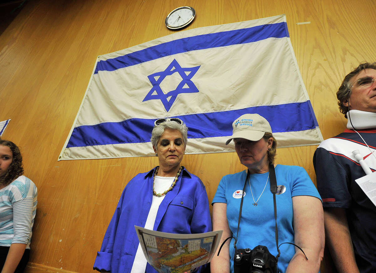 Gail G. Trell, left, and Johnna Freud, both of Stamford, look over literature as Mark Langfan, chair of the board of the Americans for a Safe Israel, speaks during the Fairfield County Rally for Solidarity, Security and Peace at the Jewish Community Center in Stamford, Conn., on Wednesday, July 23, 2014.
