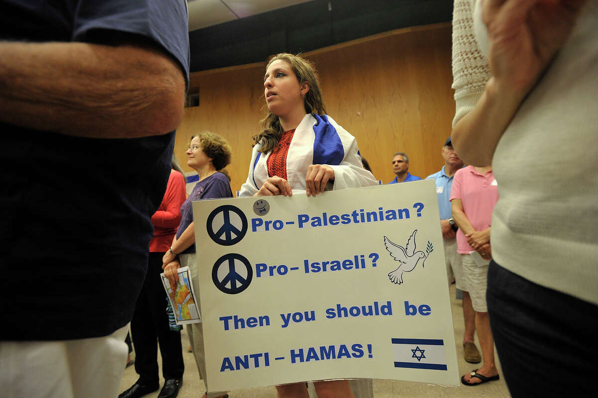 Wearing the Israeli flag, Allison Zur, of Stamford, holds a sign during the Fairfield County Rally for Solidarity, Security and Peace at the Jewish Community Center in Stamford, Conn., on Wednesday, July 23, 2014.