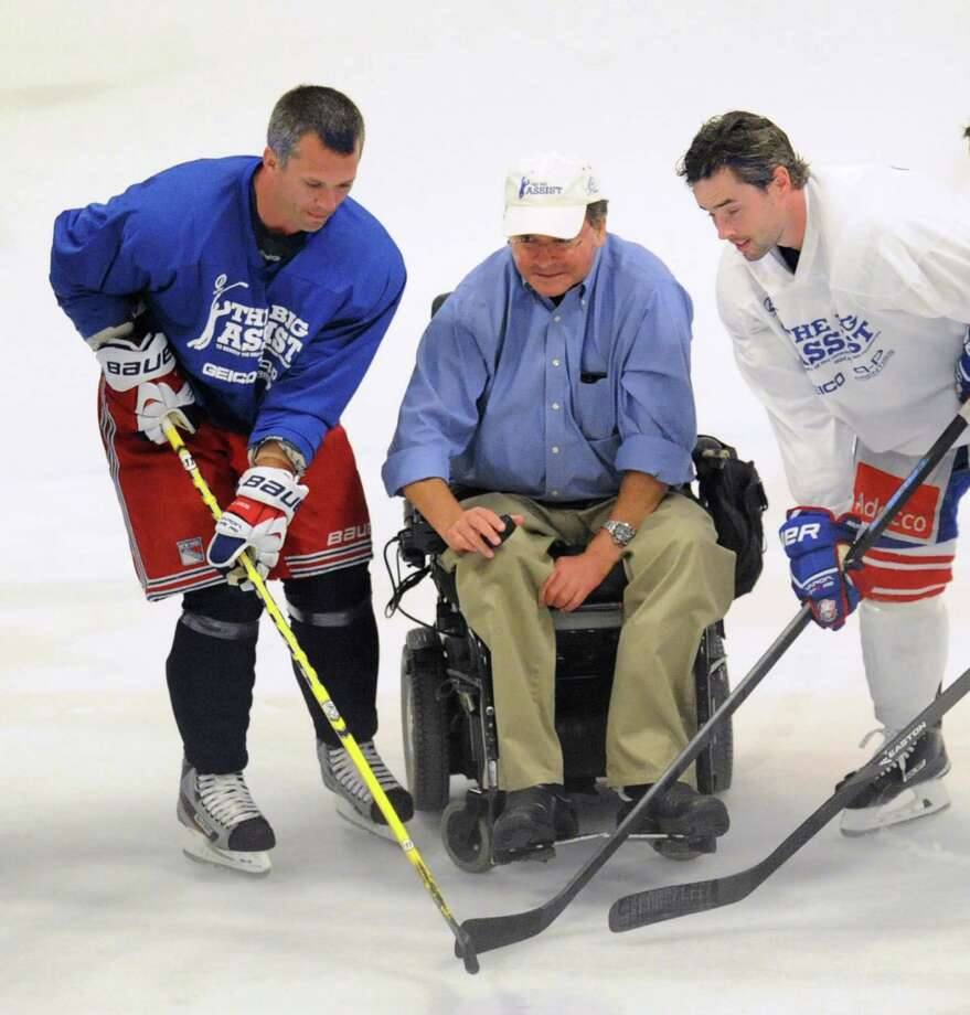 "At left, New York Ranger, Martin St. Louis (#26), a Greenwich resident, with Obie Harrington-Howes, at center, and Darien's Ryan Shannon of the Zurich Lions of the Swiss National League, during the ceremonial puck-drop at the start of NHL superstars Big Assist exhibtion game to benefit the Obie Harrington-Howes Foundation at Terry Conners Rink in Stamford, Conn., Wednesday night, July 23, 2014.  The Obie Harrington-Howes Foundation's stated mission is ""dedicated to maintaining and improving quality of life by providing financial aid to individuals with spinal cord injuries,"" and was originally established by members of the Darien community in response to Obie's spinal-cord injury in a swimming accident on July 4, 1997, which left him paralyzed. Photo: Bob Luckey / Greenwich Time"