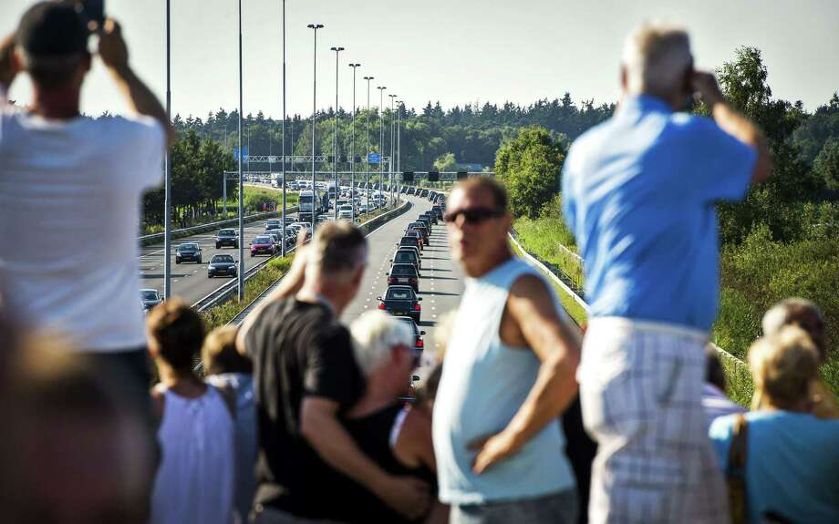 Mourners watch from a bridge a convoy of hearses carrying coffins containing the remains of victims of the downed Malaysia Airlines flight MH17, driving from the Eindhoven Airbase to Hilversum near Boxtel on July 23, 2014, after a ceremony following the arrival of a Dutch Air Force C-130 Hercules plane and an Australian Royal Australian Air Force C17 transport plane with the first bodies of the 298 victims of the Malaysia Airlines MH17 plane crash in eastern Ukraine.  Photo: REMKO DE WAAL, AFP/Getty Images / AFP