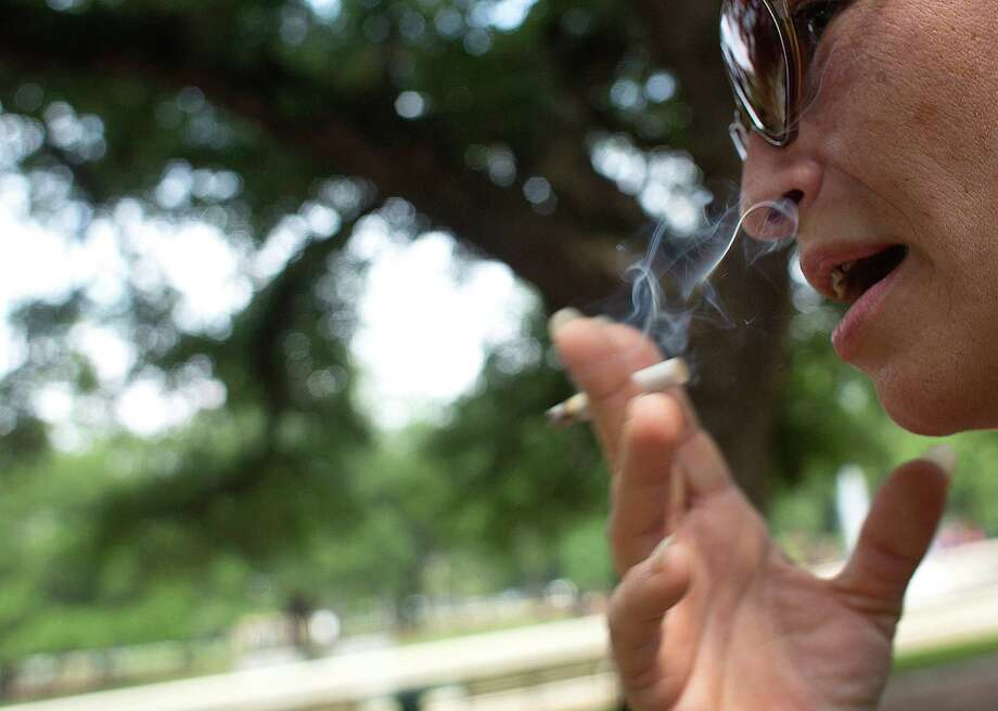 Susan Jones takes a puff Wednesday in Hermann Park, where a new smoking ban goes into effect Sept. 2. Photo: Johnny Hanson, Staff / © 2014  Houston Chronicle