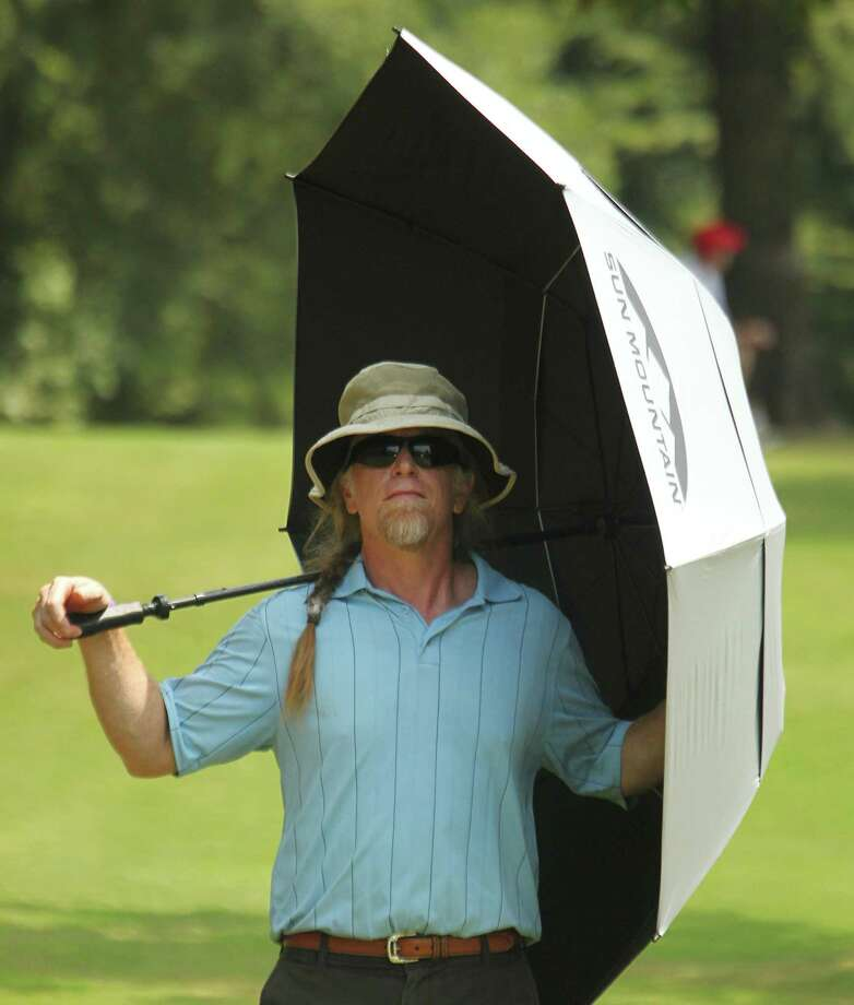 Eric Kuykendall of Austin walks with his umbrella using it for a little shade while watching the U.S. Junior Amateur Championship Wednesday July 23, 2014 at The Club at Carlton Woods Nicklaus Course in The Woodlands, TX. Photo: Billy Smith II, Chronicle / © 2014 Houston Chronicle