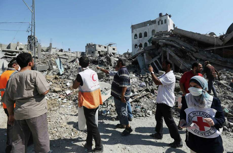 Members of humanitarian organizations inspect the damage during a two-hour temporary cease-fire in Gaza City's Shijaiyah neighborhood, Wednesday, July 23, 2014. Israeli troops battled Hamas militants on Wednesday near a southern Gaza Strip town as U.S. Secretary of State John Kerry reported progress in efforts to end fighting that has so far killed hundreds of Palestinians and tens of Israelis. (AP Photo/Hatem Moussa) ORG XMIT: HM111 Photo: Hatem Moussa / AP