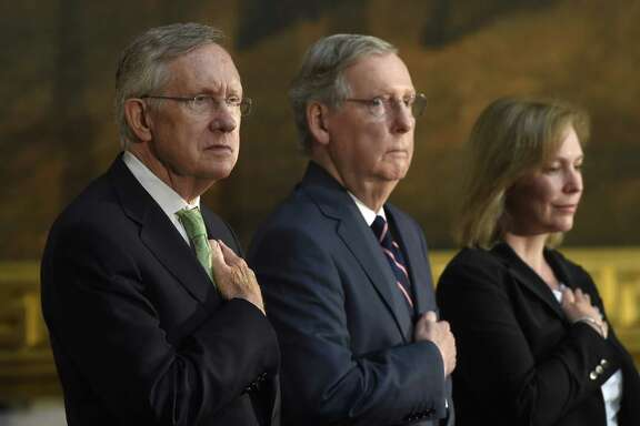 FILE - This July 9, 2014, file photo shows, from left, Senate Majority Leader Harry Reid of Nev., Senate Minority Leader Mitch McConnell of Ky., and Sen. Kirsten Gillibrand, D-N.Y., as they listen to the National Anthem during a ceremony on Capitol Hill in Washington. The Senate voted to advance an election-year bill limiting tax breaks for U.S. companies that move operations overseas. But big hurdles remain. (AP Photo/Susan Walsh, File)