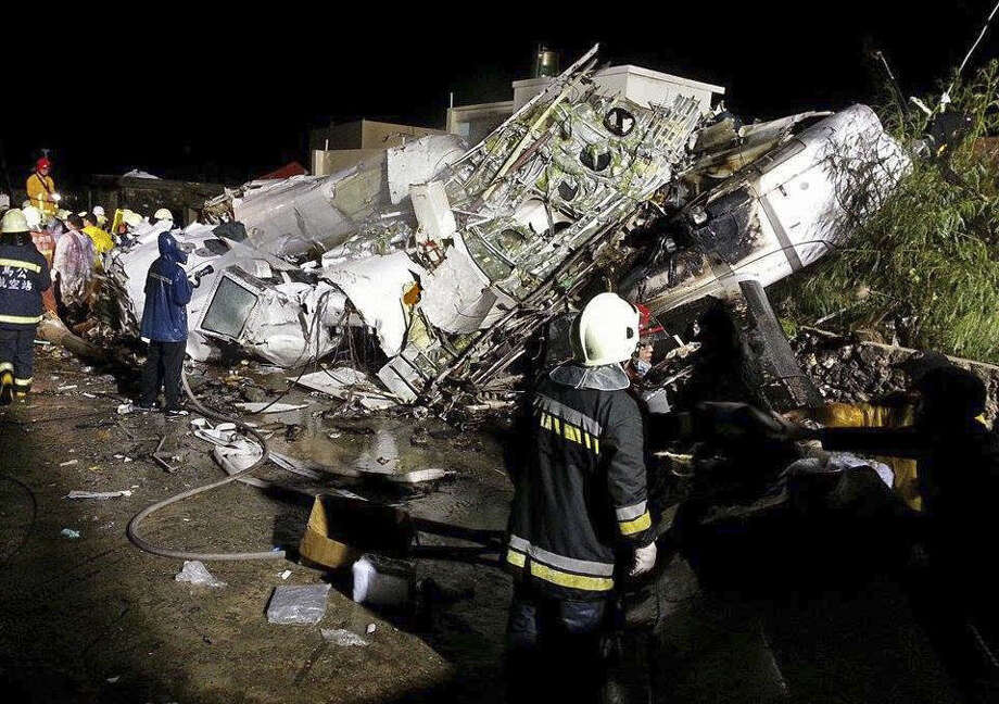Rescue workers survey the wreckage of TransAsia Airways flight GE222, which crashed while attempting to land in stormy weather on the Taiwanese island of Penghu late Wednesday. Photo: Wong Yao-wen / Associated Press / AP