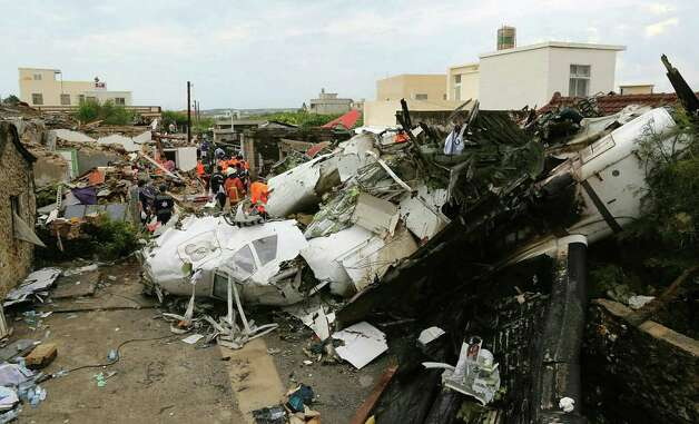 Rescue workers survey the wreckage of TransAsia Airways Flight GE222 on the Taiwanese island of Penghu Thursday, July 24, 2014. The plane attempting to land in stormy weather crashed on the island late Wednesday, killing more than 40 people and wrecking houses and cars on the ground. (AP Photo) TAIWAN OUT ORG XMIT: TPE801 / AP