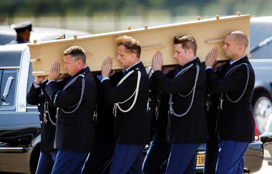 Pallbearers carry a coffin towards a hearse during a ceremony to mark the return of the first bodies, of passengers and crew killed in the downing of Malaysia Airlines Flight 17, from Ukraine at Eindhoven military air base, Netherlands, Wednesday, July 23, 2014. After being removed from the planes, the bodies were taken in a convoy of hearses to a military barracks in the central city of Hilversum, where forensic experts will begin the painstaking task of identifying the bodies and returning them to their loved ones. (AP Photo/Phil Nijhuis) ORG XMIT: AMS120 Photo: Phil Nijhuis / AP