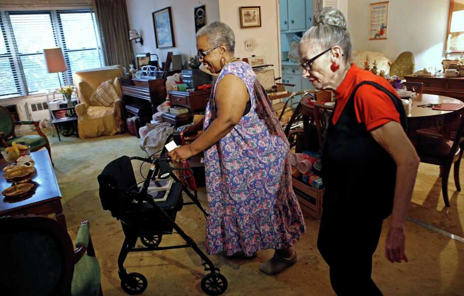 In this July 17, 2014 photo, Carolyn Allen, left, a 69-year-old widow who has suffered two strokes, makes her way to the living room with roommate Marcia Rosenfeld, who owns the apartment Allen lives in New York. The two women are roommates thanks to a home-sharing program run by a New York-based nonprofit agency. Rosenfeld's two-bedroom apartment is too big for her, and even with a senior citizen's rent break, at over $1,000 a month, it was too expensive, so she is happy to have Allen help share living expenses. Allen doesn't want to live alone and doesn't want to spend a lot on rent, so she and Rosenfeld agree the program suits their individual needs. (AP Photo/Kathy Willens) ORG XMIT: NYKW201 Photo: Kathy Willens / AP