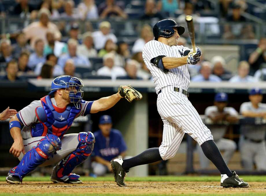NEW YORK, NY - JULY 23:  Brett Gardner #11 of the New York Yankees hits a solo home run in the third inning as Chris Gimenez #60 of the Texas Rangers defends on July 23, 2014 at Yankee Stadium in the Bronx borough of New York City.  (Photo by Elsa/Getty Images) ORG XMIT: 477586699 Photo: Elsa / 2014 Getty Images