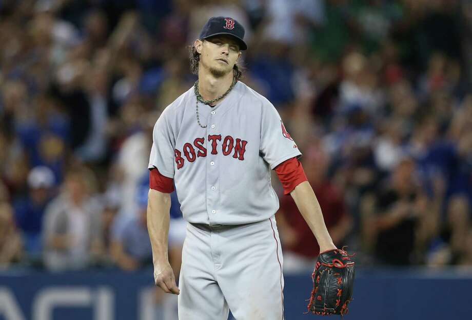 TORONTO, CANADA - JULY 23: Clay Buchholz #11 of the Boston Red Sox reacts after a throwing error with two outs by Xander Bogaerts #2 led to an unearned run in the sixth inning during MLB game action against the Toronto Blue Jays on July 23, 2014 at Rogers Centre in Toronto, Ontario, Canada. (Photo by Tom Szczerbowski/Getty Images) ORG XMIT: 477586701 Photo: Tom Szczerbowski / 2014 Getty Images