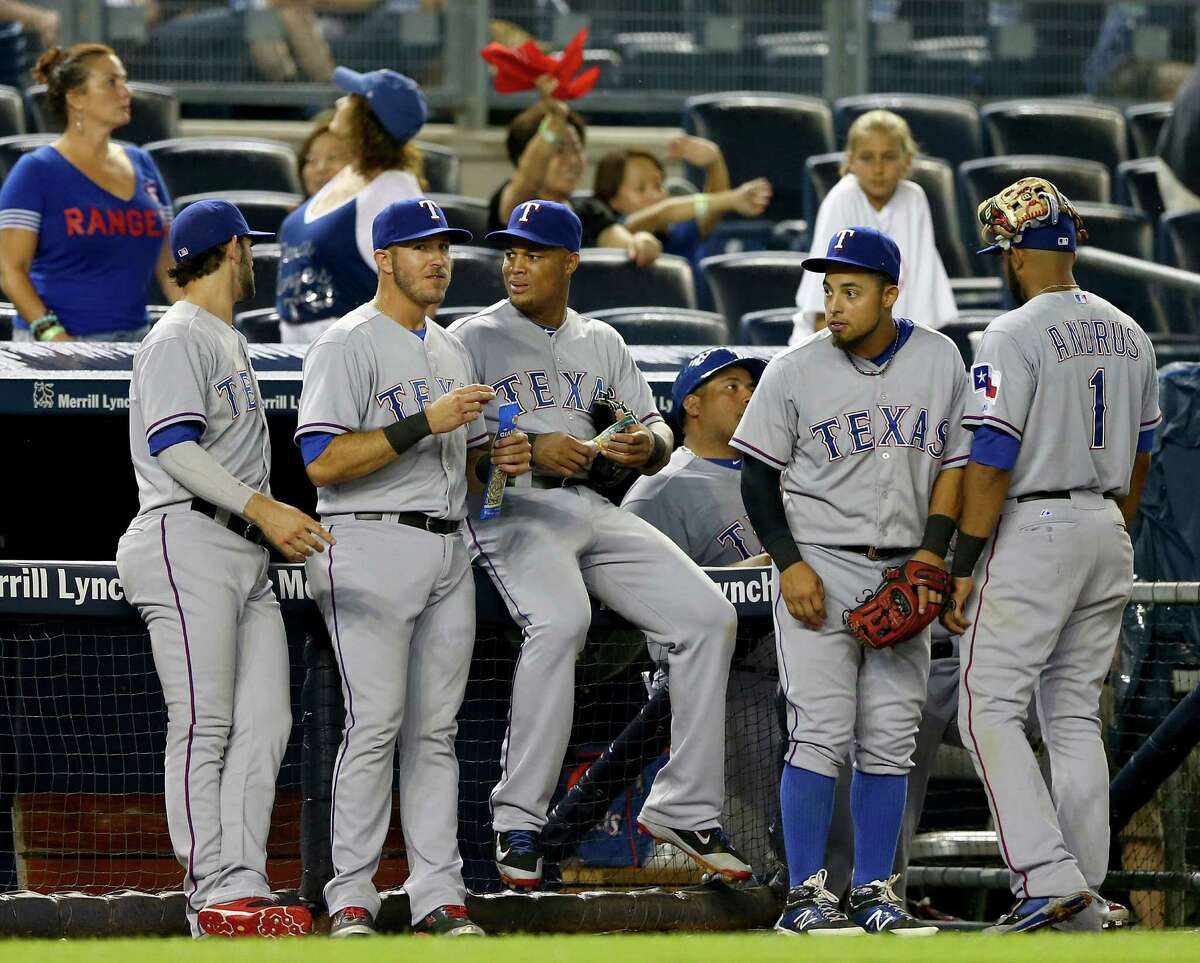 Rangers players wait as umpires and managers discuss whether to play after a rain delay. The game was called because of concerns with the field.