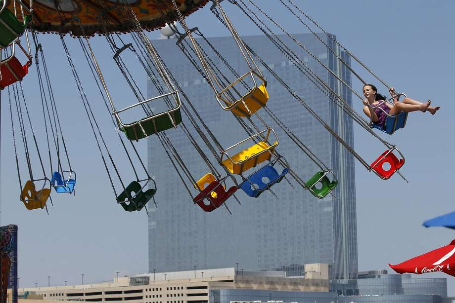 A young girl has a swing ride to herself in Atlantic City, N.J., Wednesday, July 23, 2014. (AP Photo/Mel Evans) Photo: Mel Evans, Associated Press