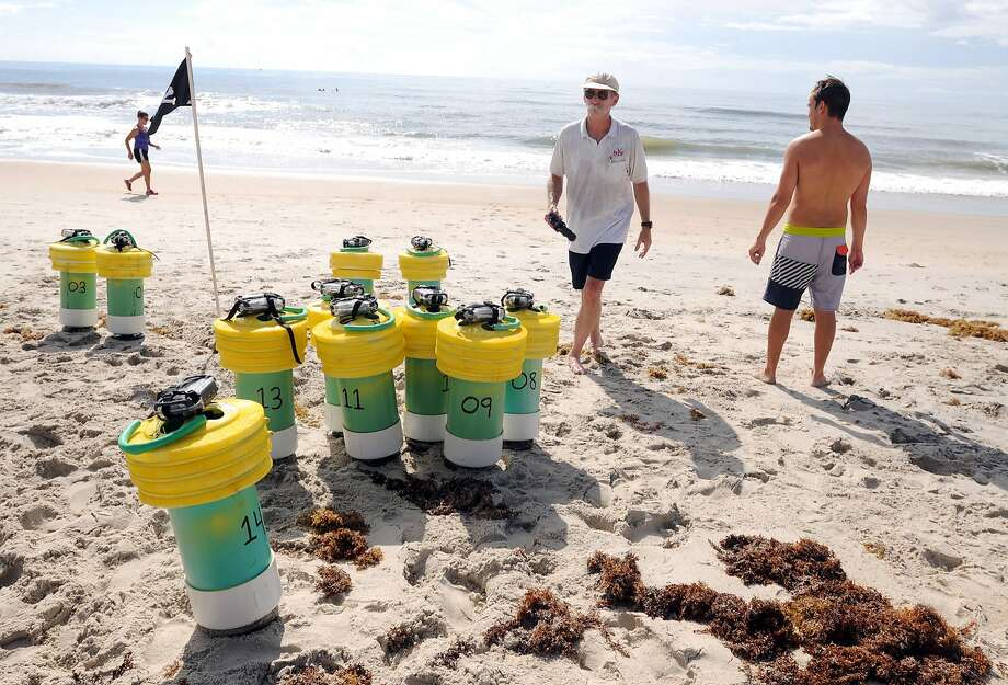 Spencer Rogers, left, coastal specialist with North Carolina Sea Grant, and Nick Cortale, University of North Carolina, Wilmington graduate student, prepare to launch buoys into the surf that will collect rip current data in Carolina Beach, N.C., Wednesday, July 23, 2014. (AP Photo/The Star-News, Mike Spencer) LOCAL TELEVISION OUT; LOCAL INTERNET OUT Photo: Mike Spencer, Associated Press