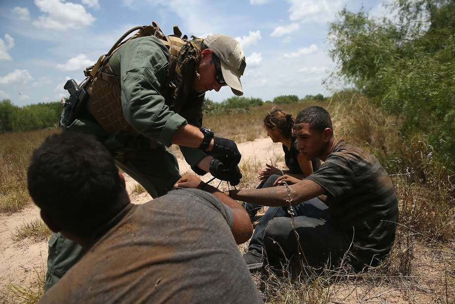FALFURRIAS, TX - JULY 23:  U.S. Border Patrol agents detain undocumented immigrants in dense brushland some 60 miles north of the U.S. Mexico border in Brooks County on July 23, 2014 near Falfurrias, Texas. Thousands of immigrants, many of them minors, have crossed illegally into the United States this year, causing a humanitarian crisis on the U.S.-Mexico border.  (Photo by John Moore/Getty Images) Photo: John Moore, Getty Images