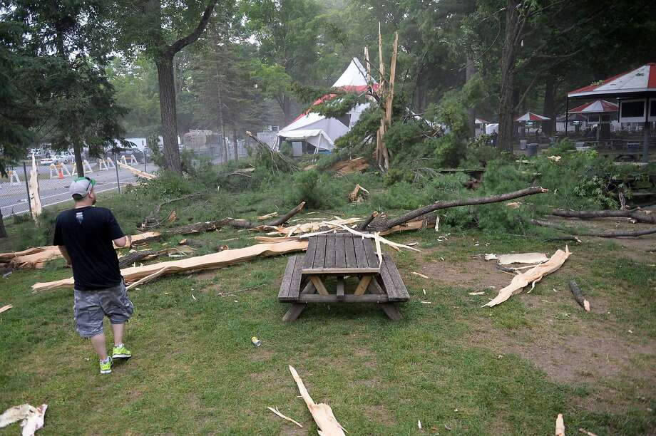People look at damage moments after lightning struck a large tree on the grounds of Saratoga Race Course in Saratoga Springs, N.Y., shortly after the last race of the day, Wednesday, July 23, 2014. (AP Photo/Daily Gazette, Patrick Dodson) Photo: Patrick Dodson, Associated Press