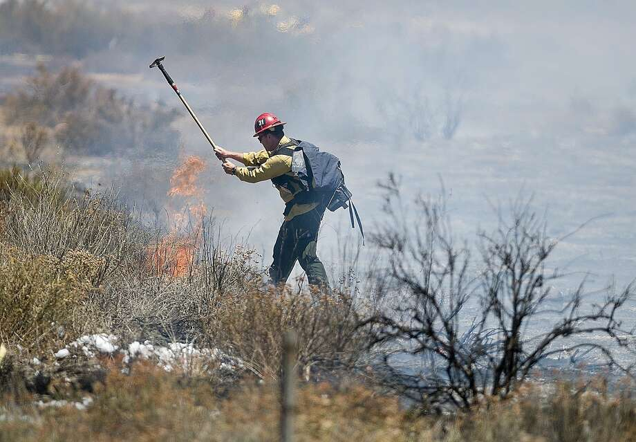 U.S. Forest Service firefighters attack a 4-acre brush fire between the north- and southbound lanes of Interstate 15 on Wednesday, July 23, 2014, in the Cajon Pass in California. U.S. Forest Service, Calfire and San Bernardino County firefighters all participated in fighting the fire. (AP Photo/Victor Valley Dally Press, James Quigg) Photo: James Quigg, Associated Press