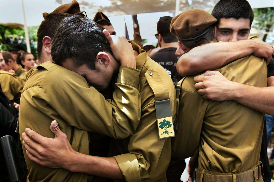 TOPSHOTS Israeli soldiers grieve during the funeral of comrade Max Steinberg on July 23 2014 at the Mount Herzl military cemetery in Jerusalem. Steinberg, a 24-year-old US-Israeli double national, is one of two American members of the Israeli army who were killed in Gaza fighting earlier this week.  AFP PHOTO/MENAHEM KAHANAMENAHEM KAHANA/AFP/Getty Images Photo: Menahem Kahana, AFP/Getty Images