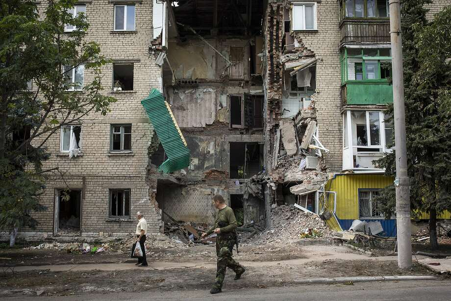 SNIZHNE, UKRAINE - JULY 23:  A pro-Russia rebel and a local resident walk past an apartment building damaged by rocket fire on July 23, 2014 in Snizhne, Ukraine. Rockets struck the town of Snizhne, a major rebel stronghold, on the morning of July 15, killing 11 people, an attack blamed on Ukraine's air force but denied by Ukrainian sources.  Two Ukrainian military fighter jets were shot down by pro-Russian separatists in the east of the country on Wednesday and the security situation is continuing to affect the investigation into the Malaysian Airlines flight MH17 crash.  Malaysian Airlines flight MH17 was travelling from Amsterdam to Kuala Lumpur when it crashed killing all 298 on board including 80 children. The aircraft was allegedly shot down by a missile and investigations continue over the perpetrators of the attack.  (Photo by Rob Stothard/Getty Images) *** BESTPIX *** Photo: Rob Stothard, Getty Images