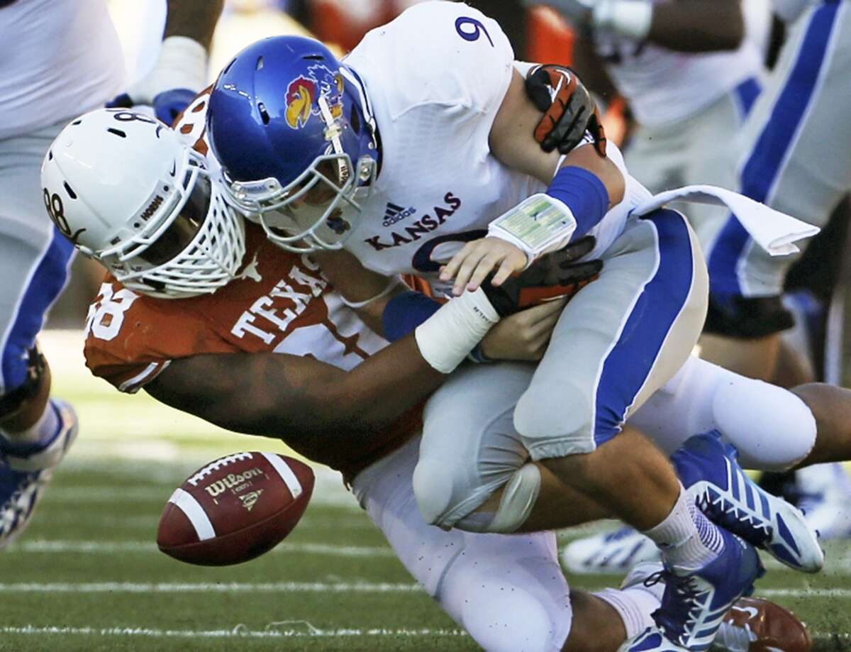 Montrel Meander forces Jayhawk quarterback Jake Heaps to fumble, resulting in fellow lineman Chris Whaley getting a touchdown as Texas hosts Kansas at Darrell K. Royal Stadium on November 2, 2013.