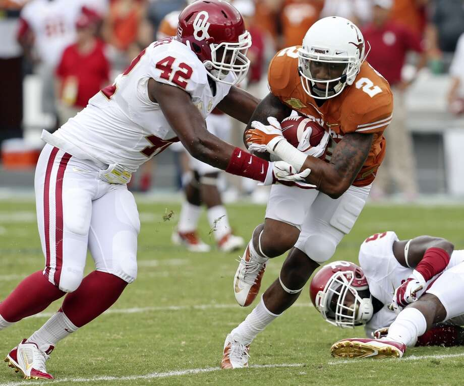 Texas Longhorns' Kendall Sanders looks for room around Oklahoma Sooners' Dominique Alexander during first half action of the Red River Rivalry, Oct. 12, 2013 at Cotton Bowl Stadium in Dallas. Photo: Edward A. Ornelas, San Antonio Express-News