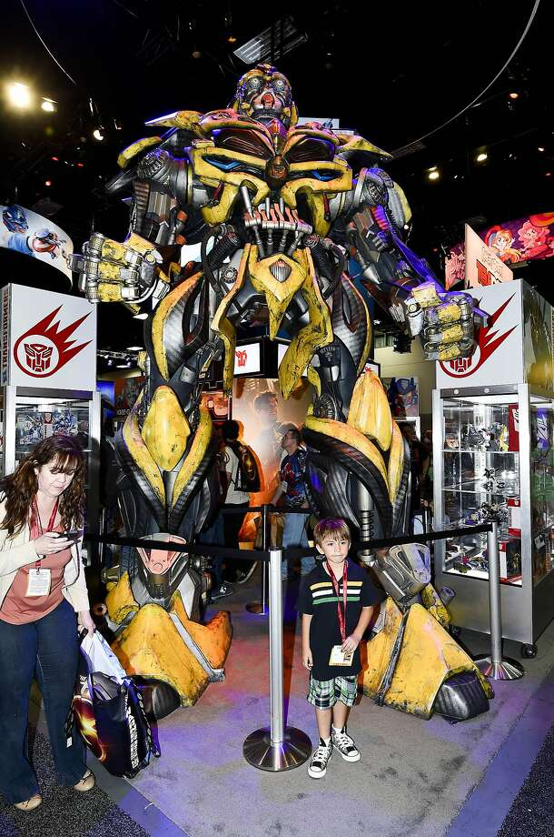 A young fan poses with a huge Transformers display during preview night at the 2014 Comic-Con International Convention held  Wednesday, July 23, 2014 in San Diego. Photo: Denis Poroy, Associated Press