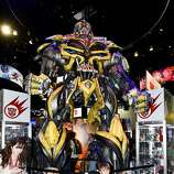A young fan poses with a huge Transformers display during preview night at the 2014 Comic-Con International Convention held  Wednesday, July 23, 2014 in San Diego.