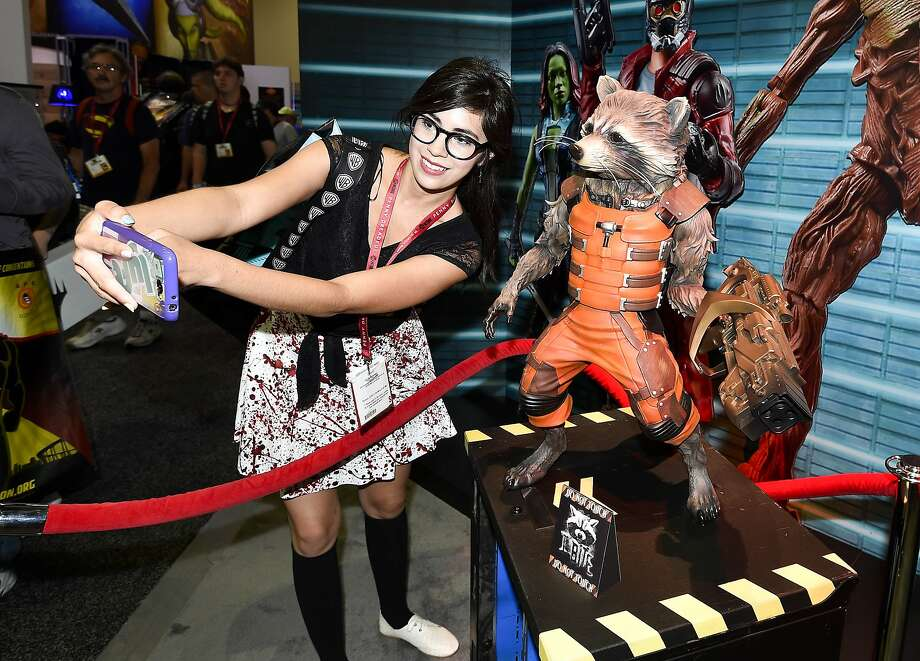 Monique Soto takes a selife with a Guardians of the Galaxy Rocket Racoon figurine during preview night at the 2014 Comic-Con International Convention held  Wednesday, July 23, 2014 in San Diego.  Photo: Denis Poroy, Associated Press