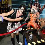 Monique Soto takes a selife with a Guardians of the Galaxy Rocket Racoon figurine during preview night at the 2014 Comic-Con International Convention held  Wednesday, July 23, 2014 in San Diego.