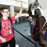 A fan high-fives another fan dressed as Star Wars' Darth Vader during preview night at the 2014 Comic-Con International Convention held  Wednesday, July 23, 2014 in San Diego.