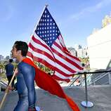 Bersain Gutierrez, dressed as Superman, carries an American flag during preview night at the 2014 Comic-Con International Convention held  Wednesday, July 23, 2014 in San Diego.
