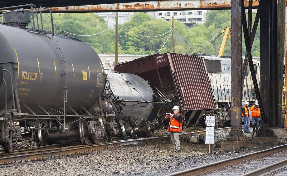 An investigator checks the scene where a train carrying crude oil went off the track under the Magnolia Bridge in Seattle on Thursday. Photo: Mike Siegel, Associated Press